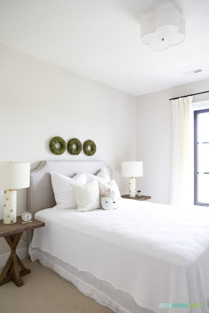 A white bedroom with wooden side table and white lamps on them. Three green wreaths above the bed.