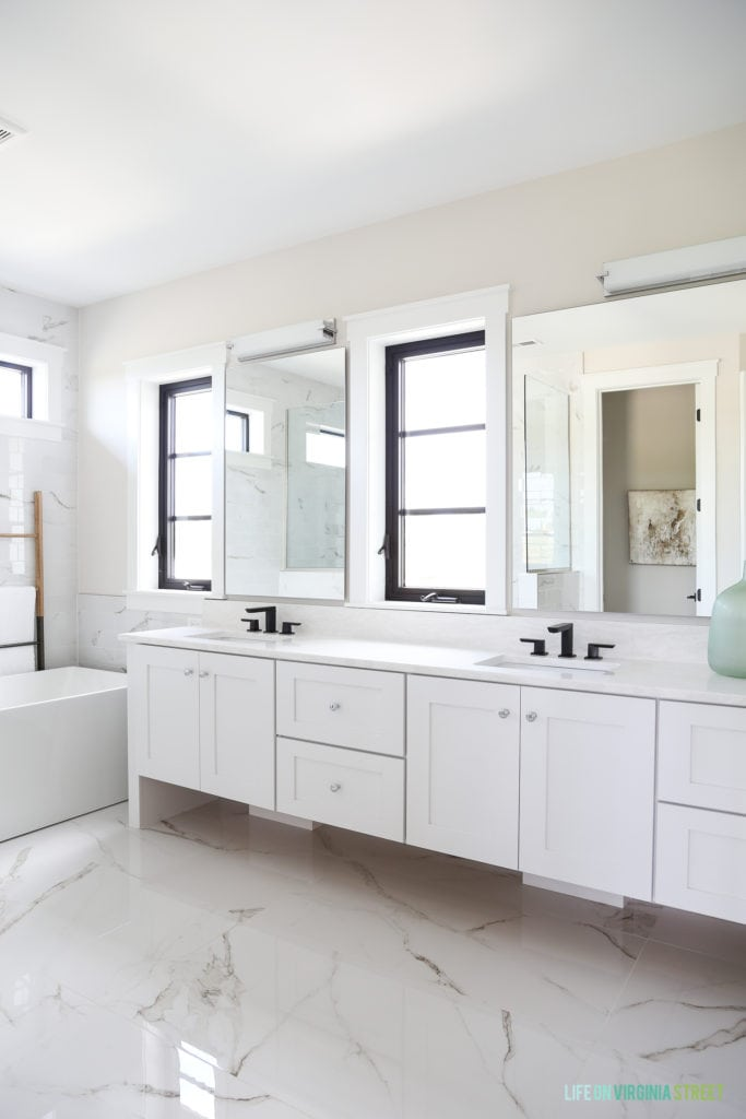 A white marble floor in master bedroom with white cabinets.
