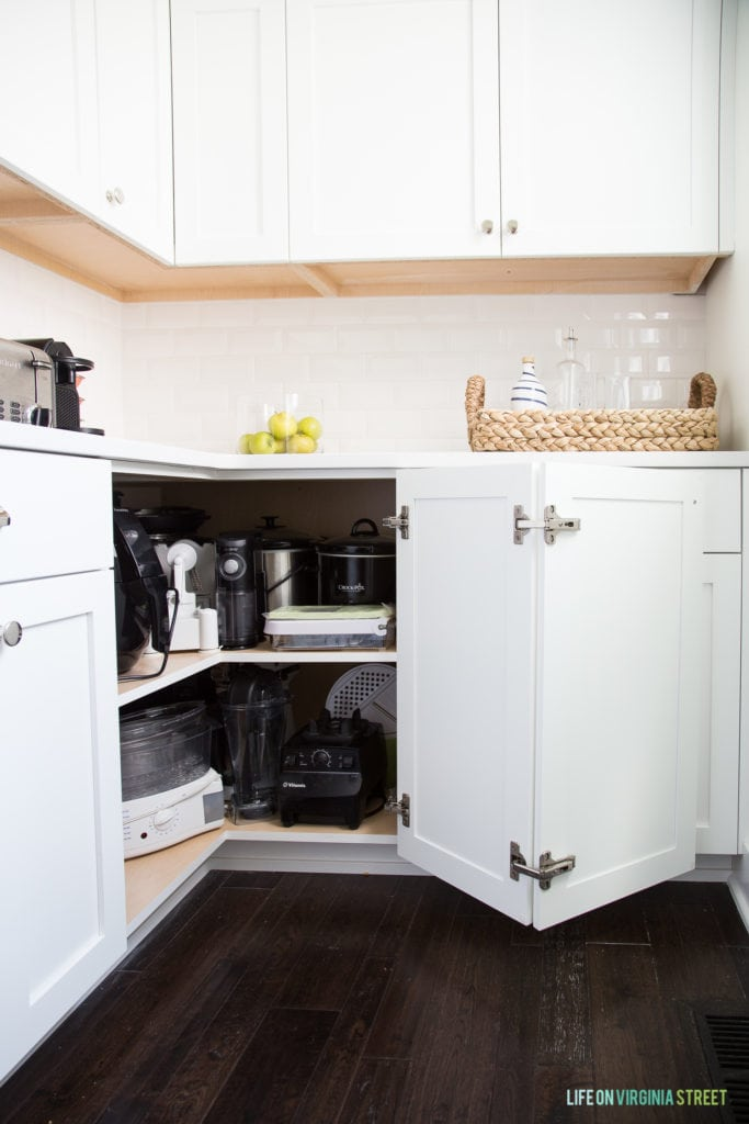 White kitchen cabinets with one corner door opened to reveal appliances inside.