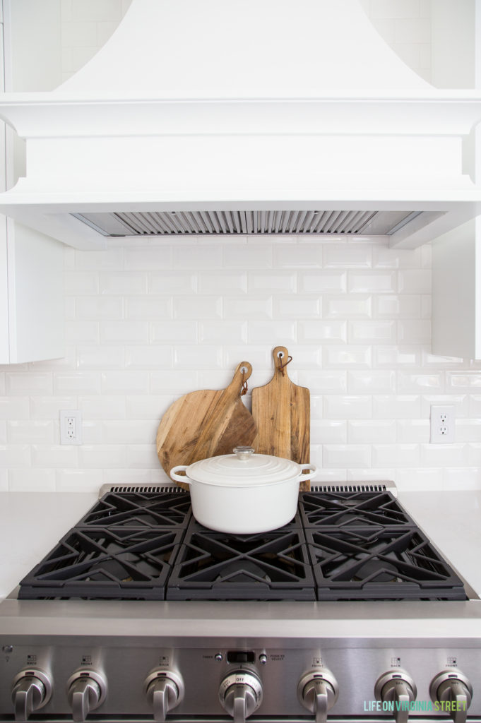 The kitchen stove with a white pot on top of it, wooden cutting boards behind it and white tile on the wall.