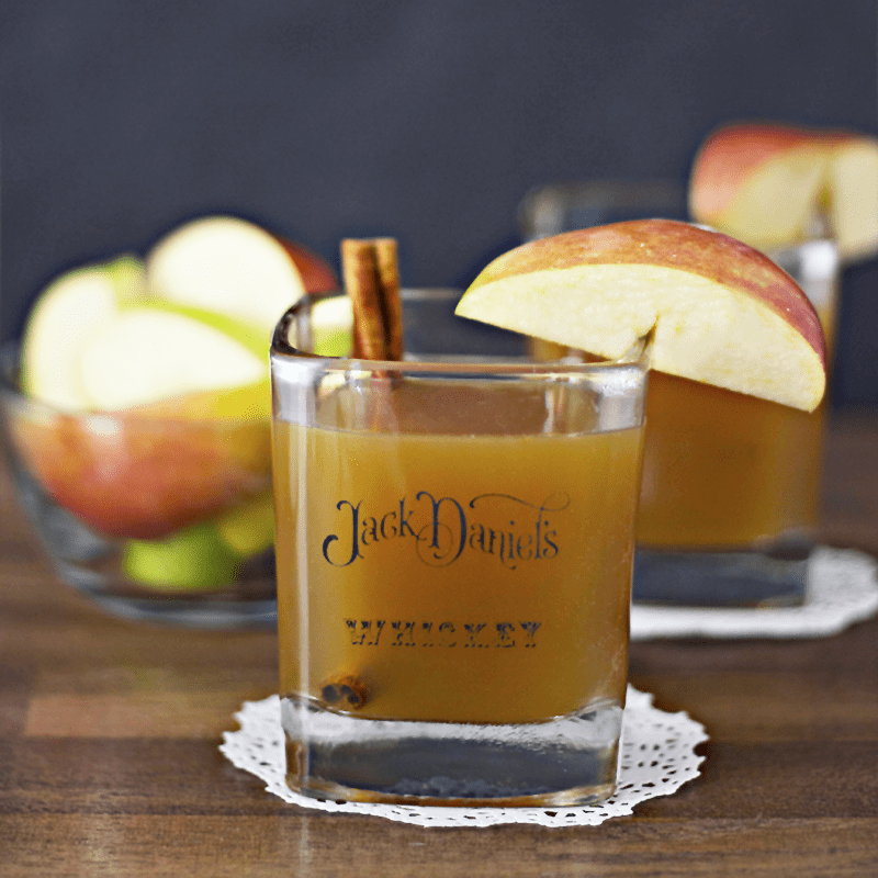 A Jack Daniels whiskey glass cocktail with an apple slice on the rim and cinnamon stick inside.