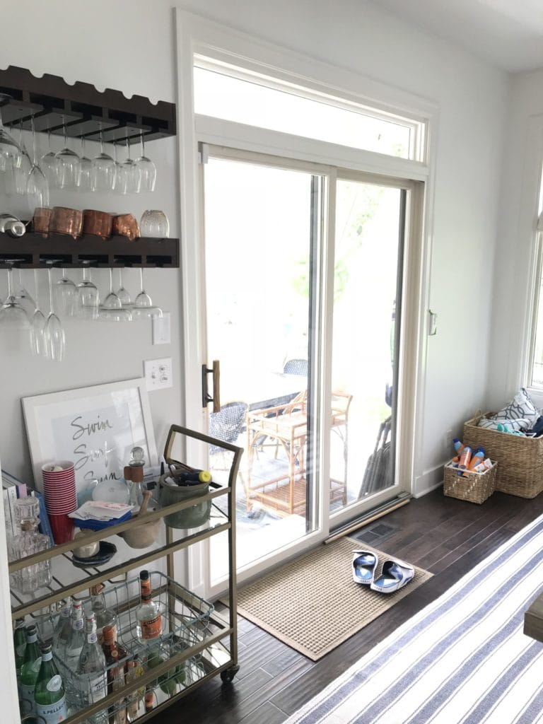 A bar cart beside a sliding glass door to the outside porch.