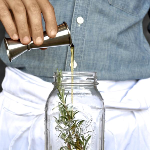 Pouring a shot into a mason jar with a sprig of greenery.