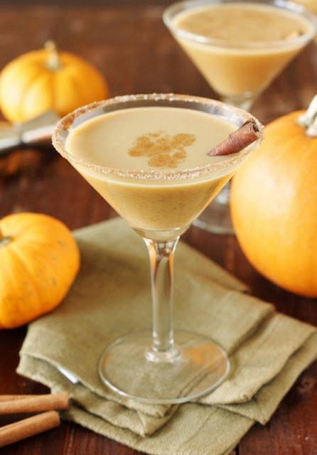 Martini glass with pumpkin martini inside and a cinnamon stick.