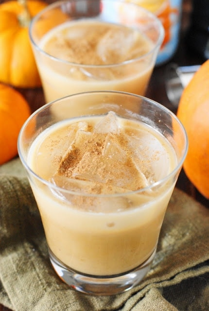Two glasses of white Russian with pumpkin in it and pumpkins around it.