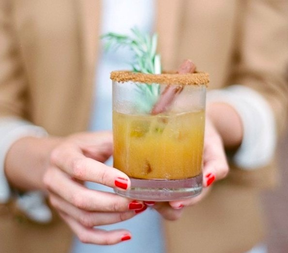 Woman holding an apple cider cocktail that has a heavily sugared rim.