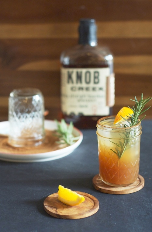 Bourbon drink in a mason jar glass with a sprig of greenery in it and a Knob bourbon bottle in the background.