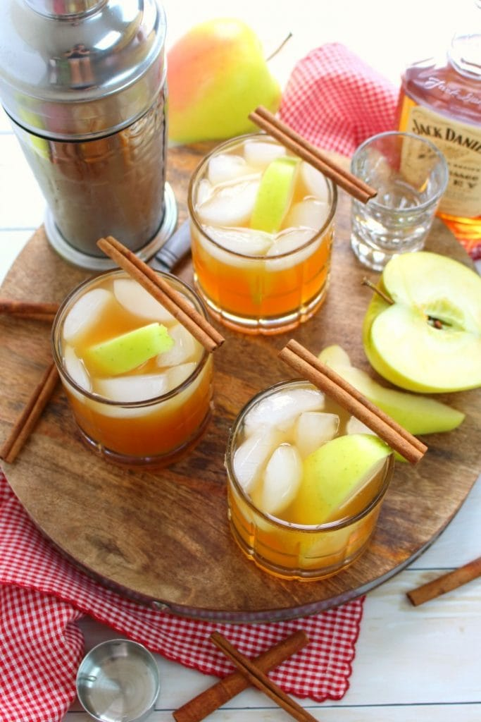 Three glasses of apple cider whiskey with a cinnamon stick on top.