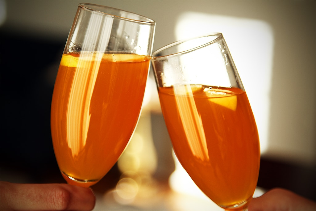 Two champagne glasses clinking with mimosa's in it.