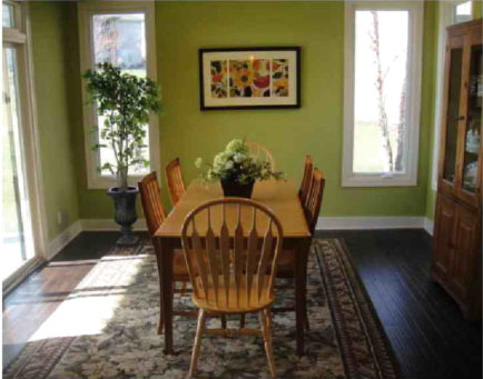 A dining room with olive green walls, a light wood table and a floral area rug.