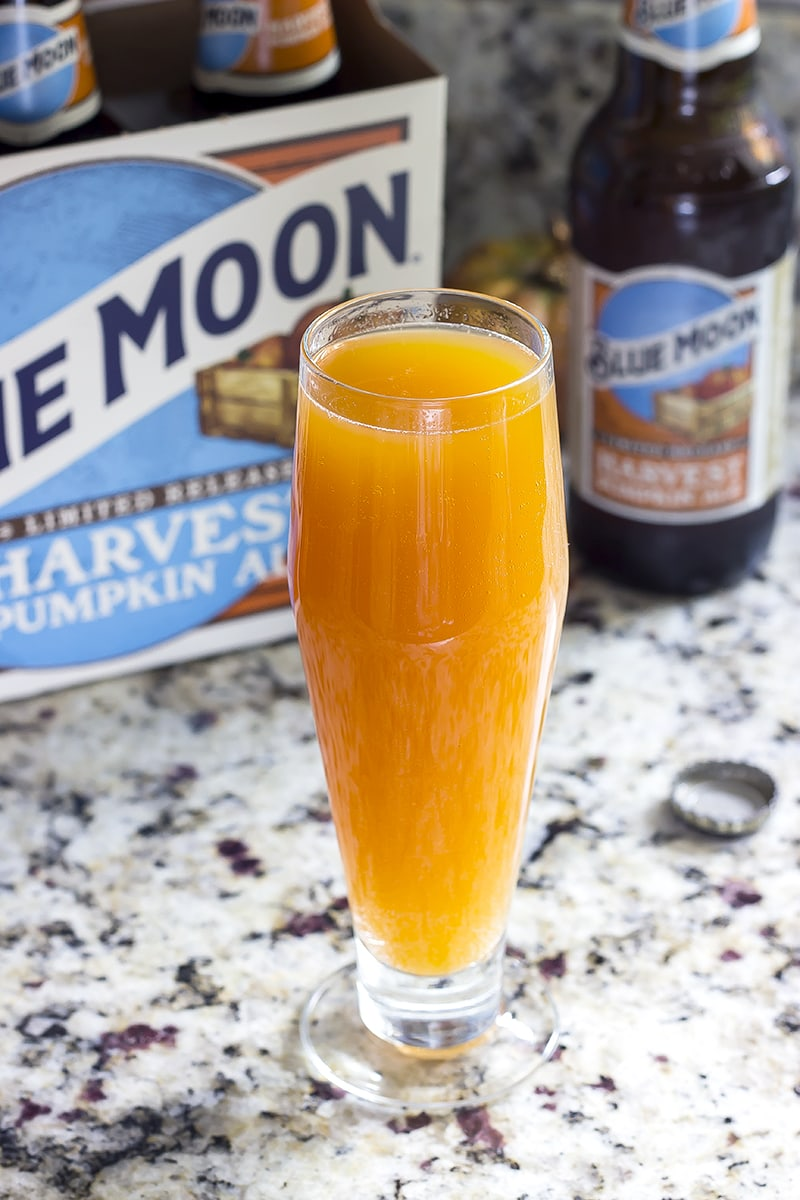 A beer glass with orange beermosa inside and a case of beer beside it on a counter.