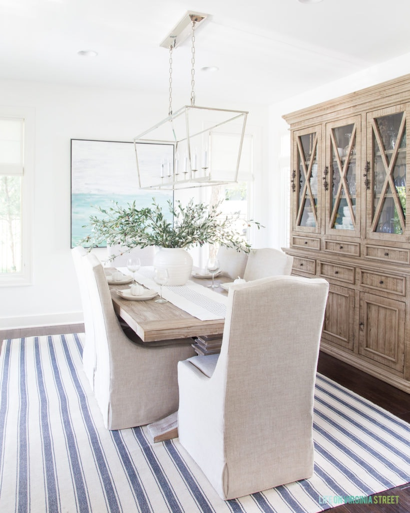 A coastal dining room with a striped rug, linen chairs, reclaimed wood hutch, blue abstract artwork, a Darlana linear pendant chandelier and faux olive leaf stems.