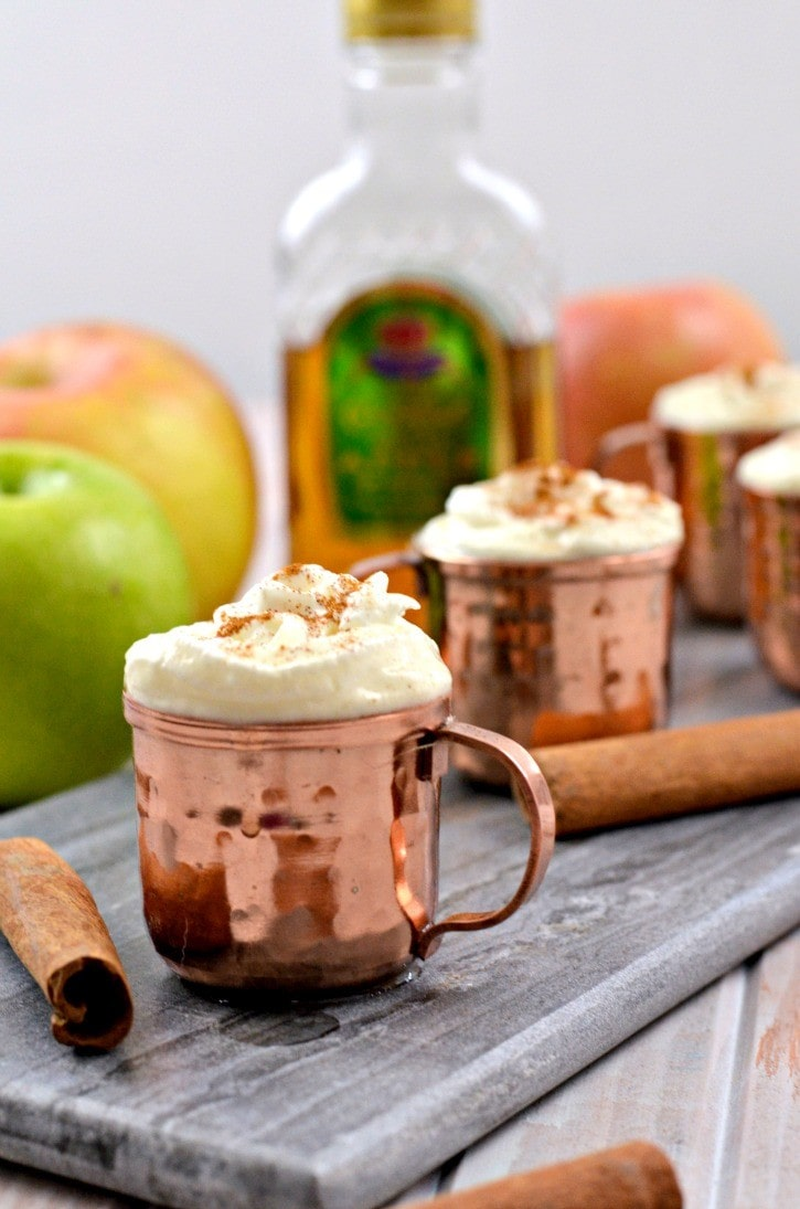Copper mugs with whip cream on a wooden bench with a crown royal bottle in the background