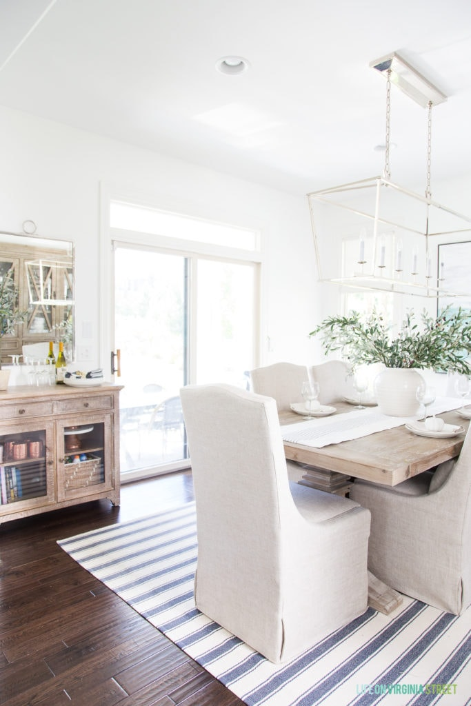 A coastal dining room with blue and white striped rug, Darlana linear chandelier, linen chairs, reclaimed wood dining table and buffet table, a silver mirror, and faux olive leaf stems.