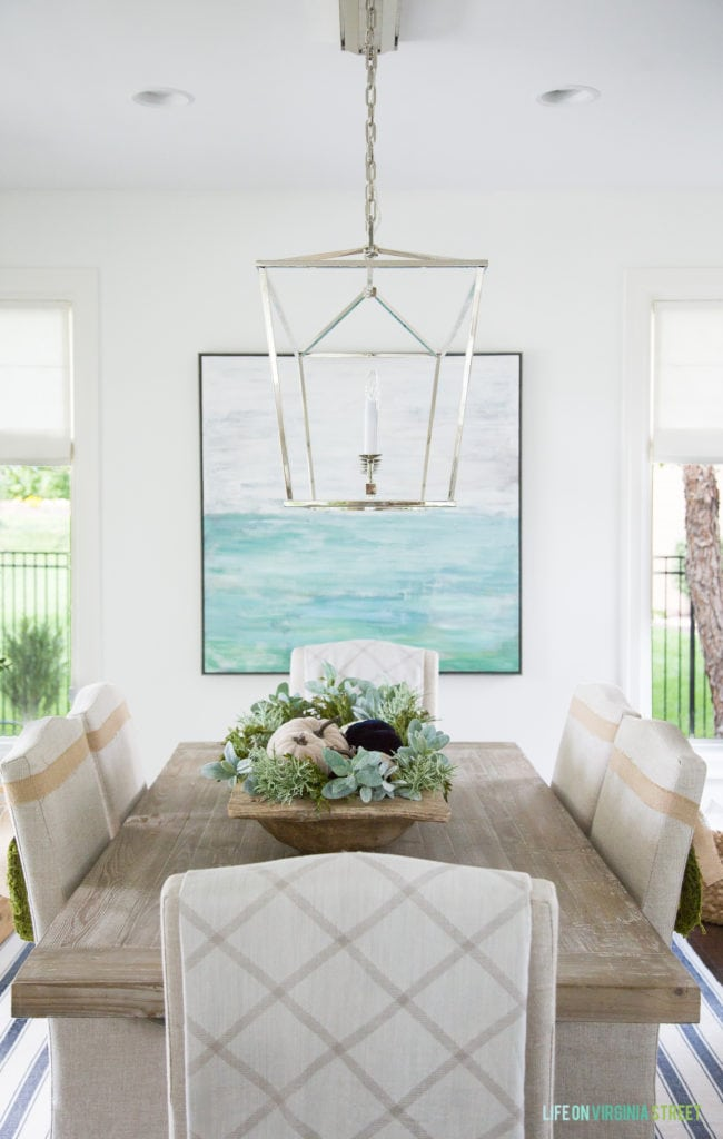 Dining table decorated for fall with chandelier over top and a ocean blue picture behind it.