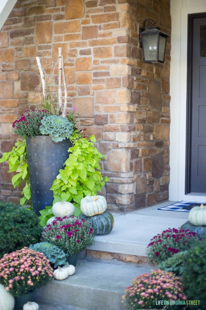 Pumpkins, large planter filled with kale, and purple and pink flowers all on the front porch.