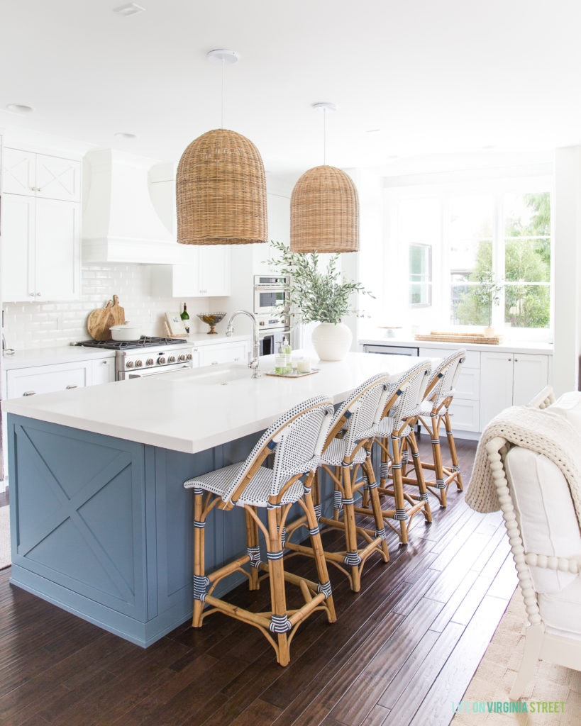 White kitchen with blue island, rattan chairs and light fixtures above the island.