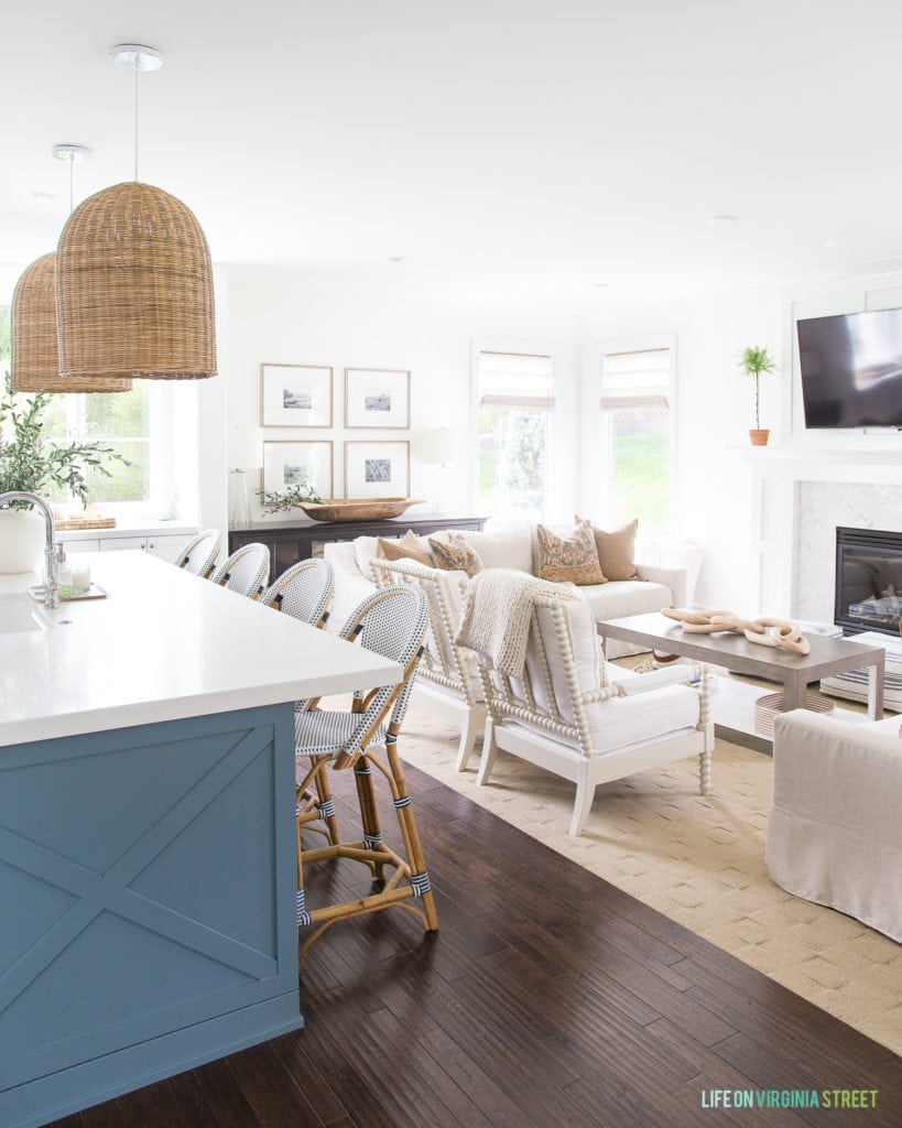 A blue kitchen island and living room decorate for fall. Includes white spindle chairs, basket pendant lights, a gallery wall with travel photos, and brown and blue accents.