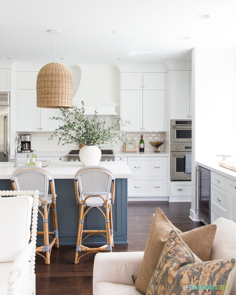 Gorgeous kitchen with white and rich blue cabinets. Love the basket pendant light fixture and the bistro style barstools. The huge pot of olive leaves is perfect for fall!