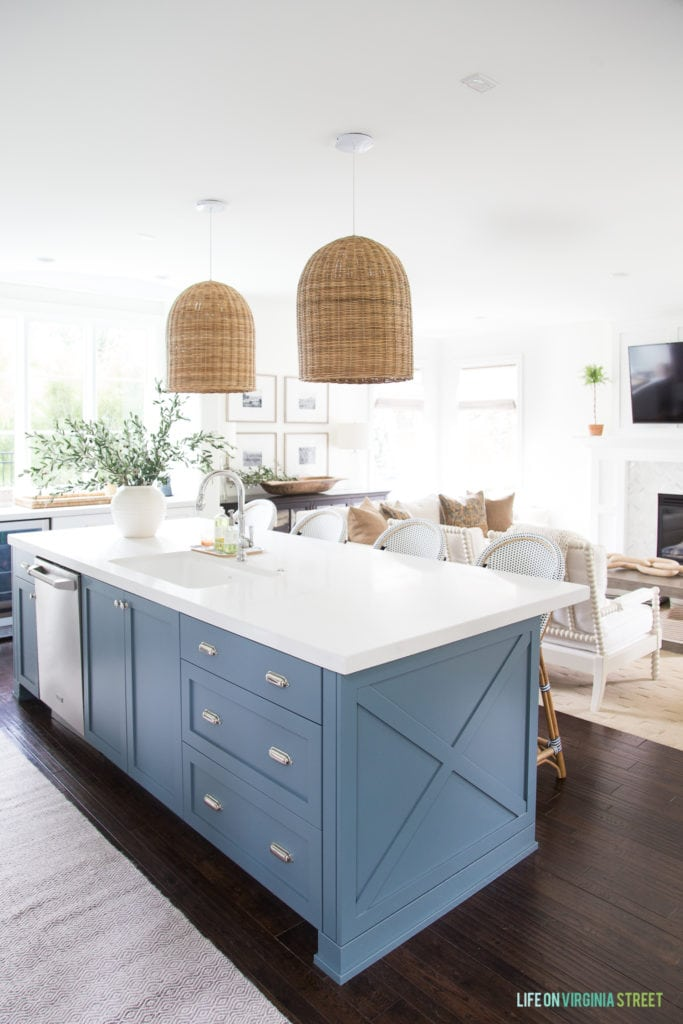 A kitchen decorated for fall. Room has white kitchen cabinets, a blue painted island, basket pendant lights, dark hardwood floors, white walls and a vase filled with olive branches.