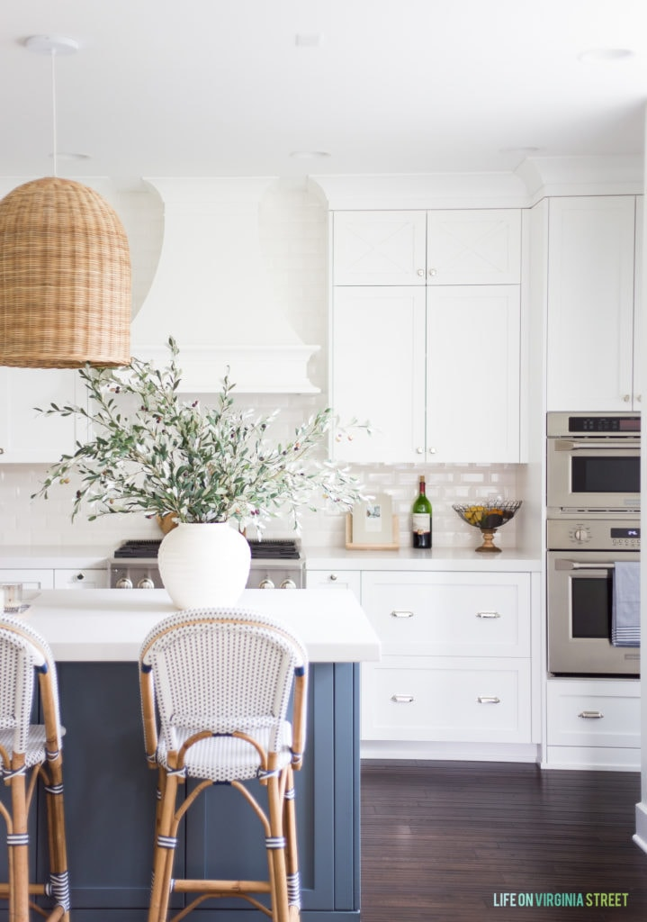 A kitchen with faux olive stems on display. This post shares all the best sources and tips for buying faux greenery!