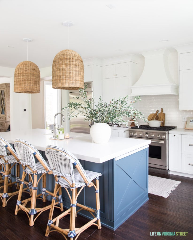A white coastal kitchen with a blue island and wood flooring.