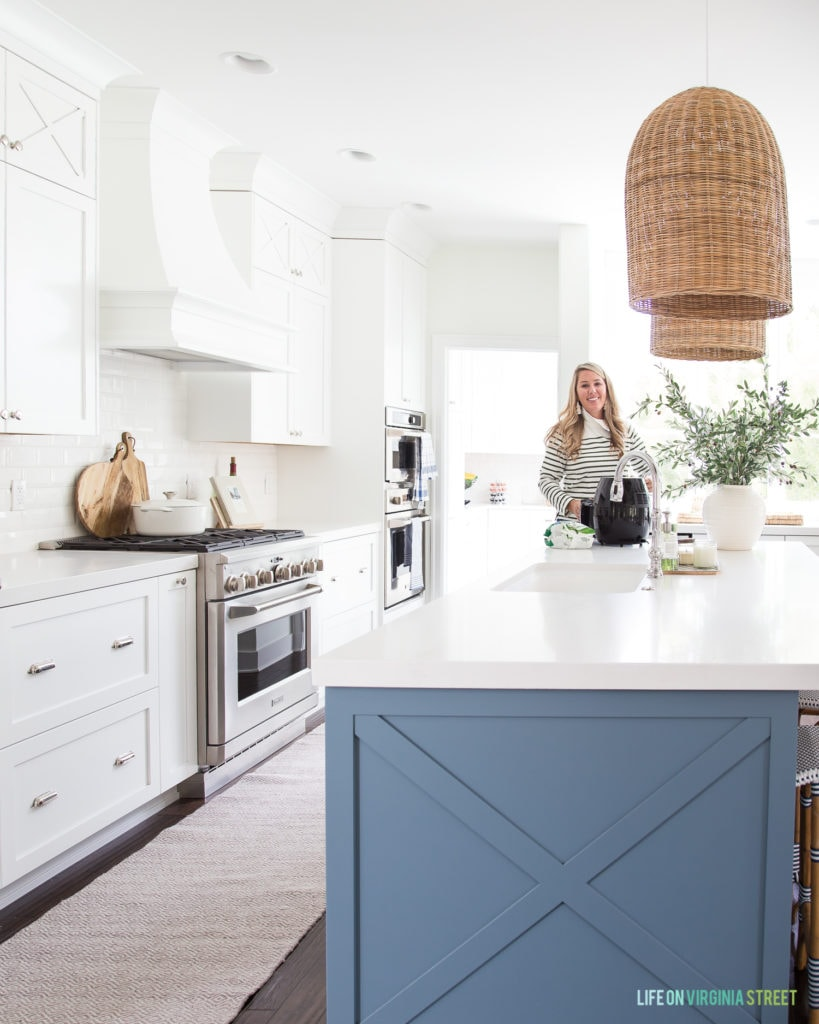 A white kitchen with a blue island and large rattan lights above the kitchen.