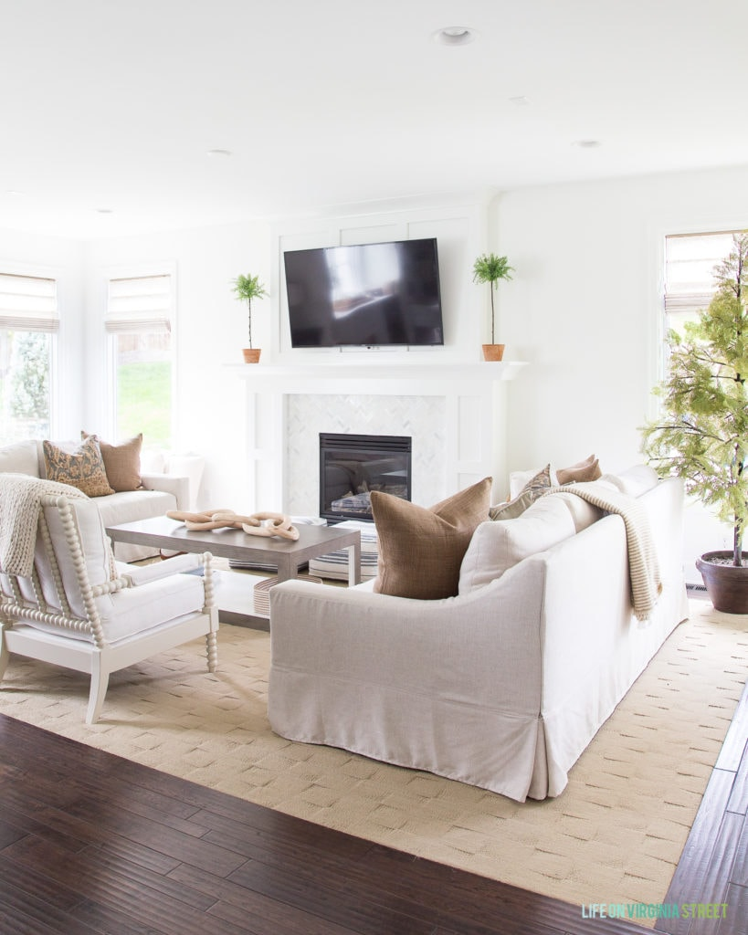 Gorgeous neutral fall living room with natural accents and shades of brown and white. I love the spindle chair, linen sofas and cypress tree!