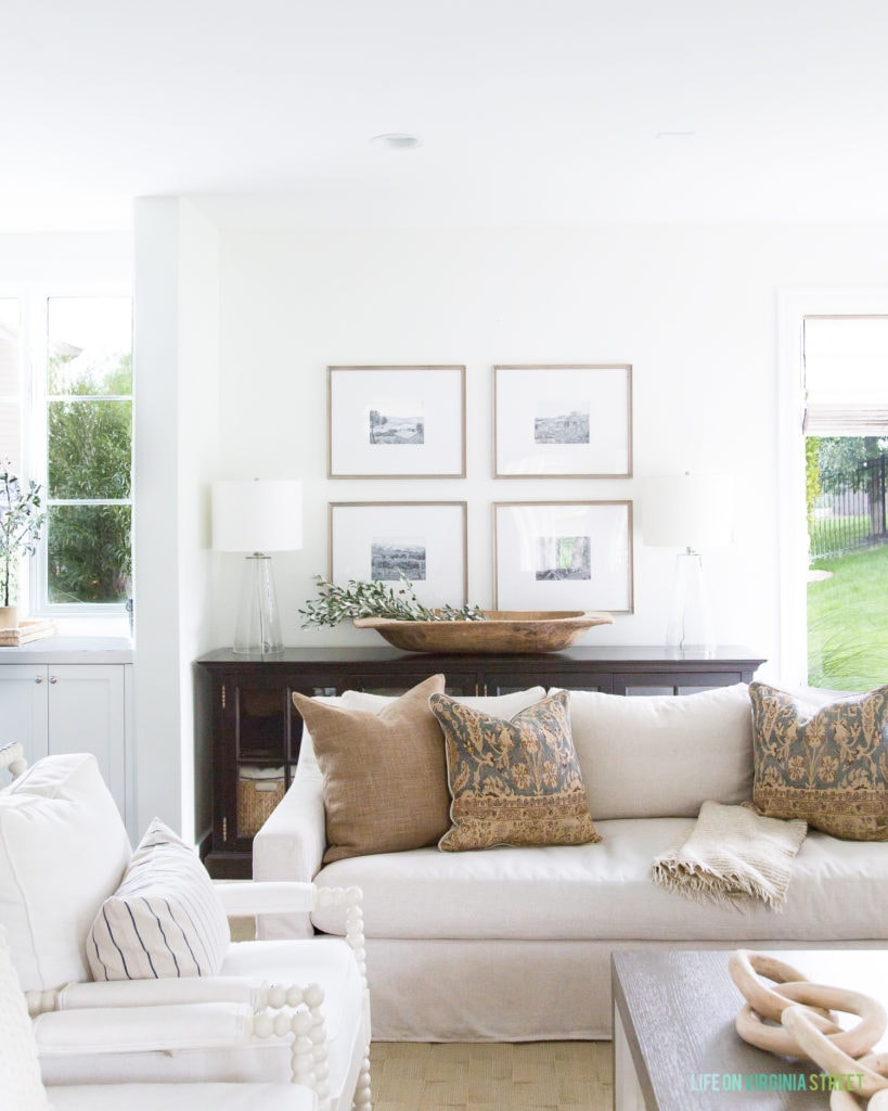 A cozy fall living room with linen sofas, white spindle chairs, bronze linen pillows, vintage style pillows, a wood dough bowl filled with olive leaves, a wood chain decor, and wood photo gallery wall.