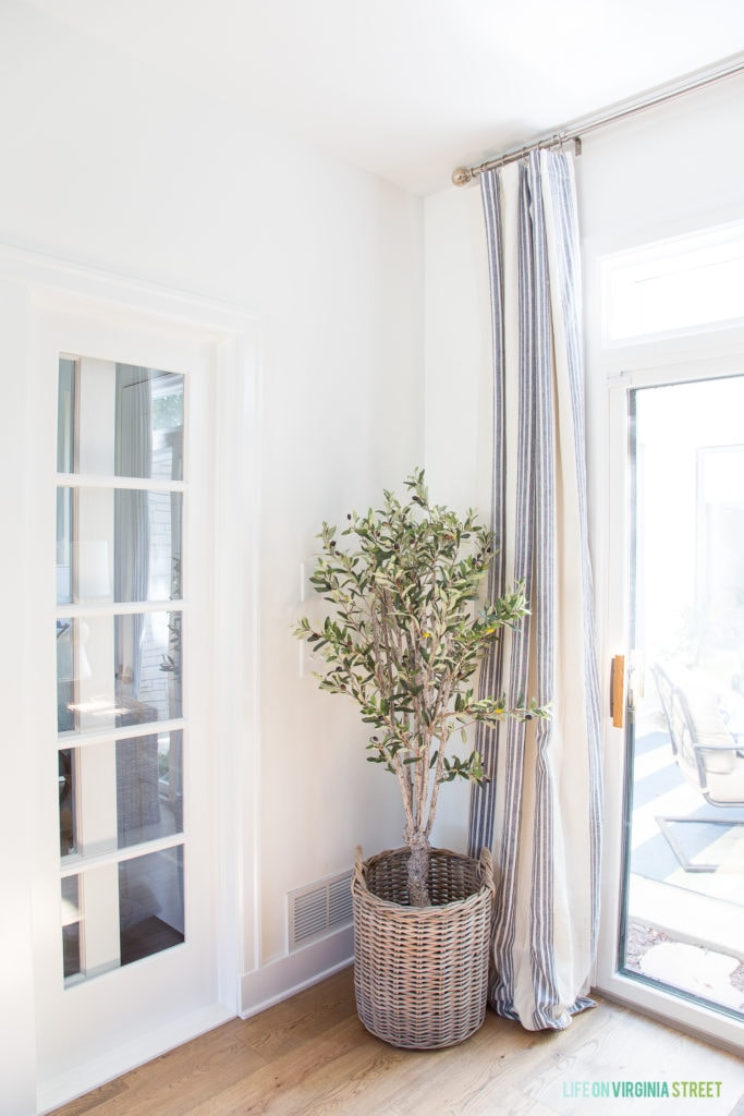 A cute faux olive tree in a woven basket is perfect fall decor! I also love the white oak floors and blue and white striped curtains!