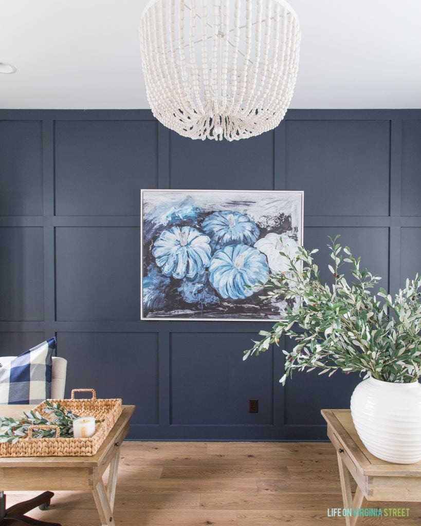 This gorgeous blue pumpkin abstract art is so perfect for fall if you love decorating with non-traditional colors! I also love the whitewashed wood bead chandelier, navy blue board and batten wall, white oak hardwood floors and the olive leaves.