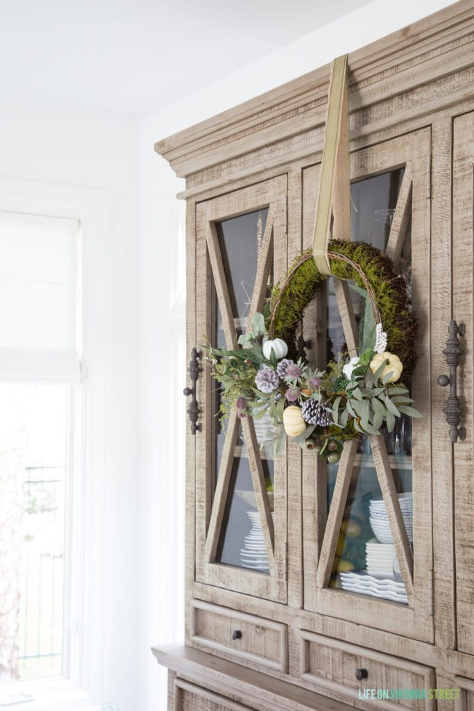 Wooden hutch with a green wreath and flowers on it in fall dining room.