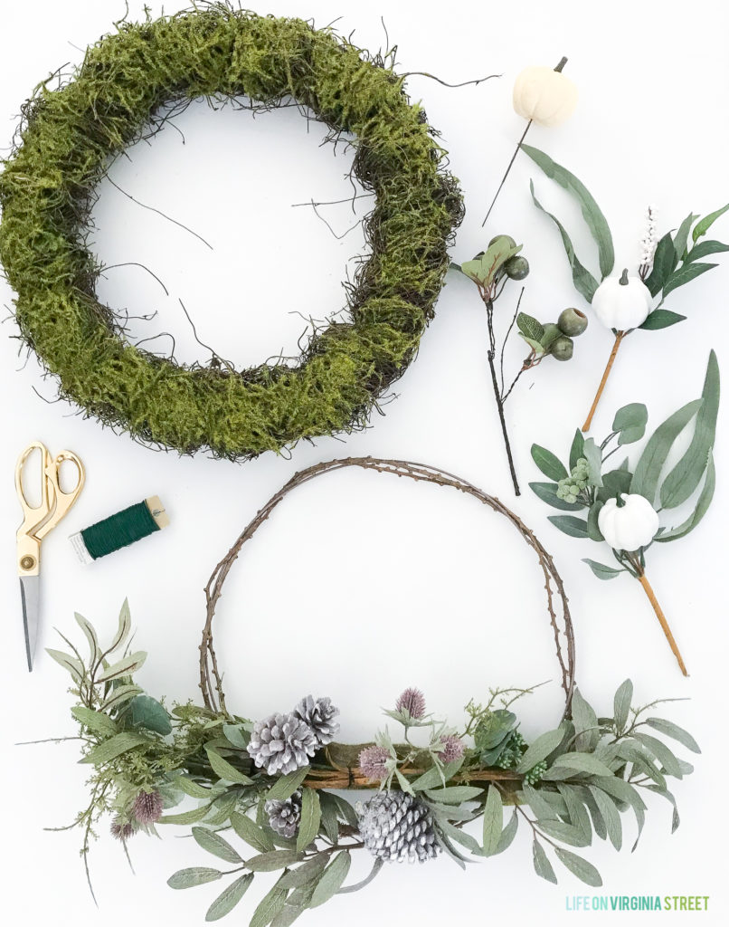 Green moss wreath and leaves with purple pinecones.