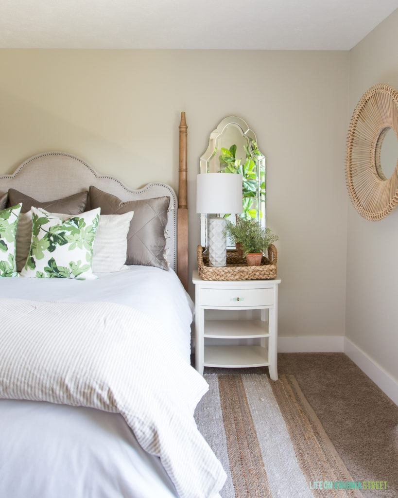 A round rattan mirror is on the side wall beside the bed.