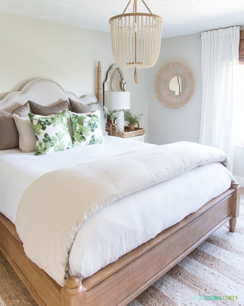 A cozy neutral fall bedroom with a beaded light hanging over the bed.