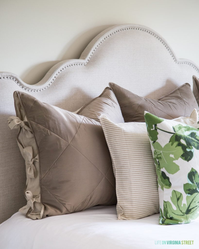 Fig leaf pillows are on the bed with neutral grey pillows.