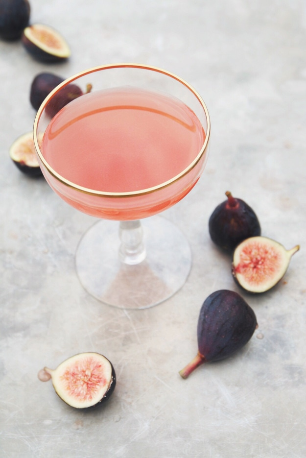 Pink cocktail in a glass with a gold rim and figs lying around it.