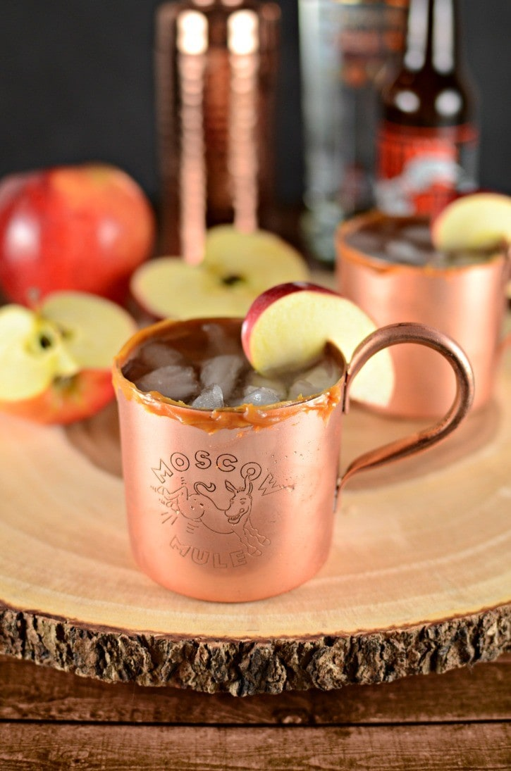 Apple cider Moscow Mule in a copper cup and an apple slice on rim.