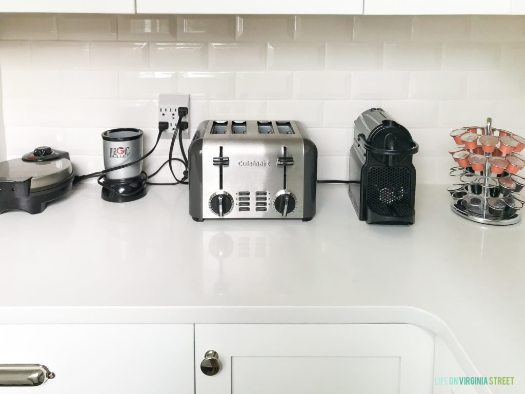 Appliances on the counter such as a toaster, coffee maker and grinder and a waffle maker.