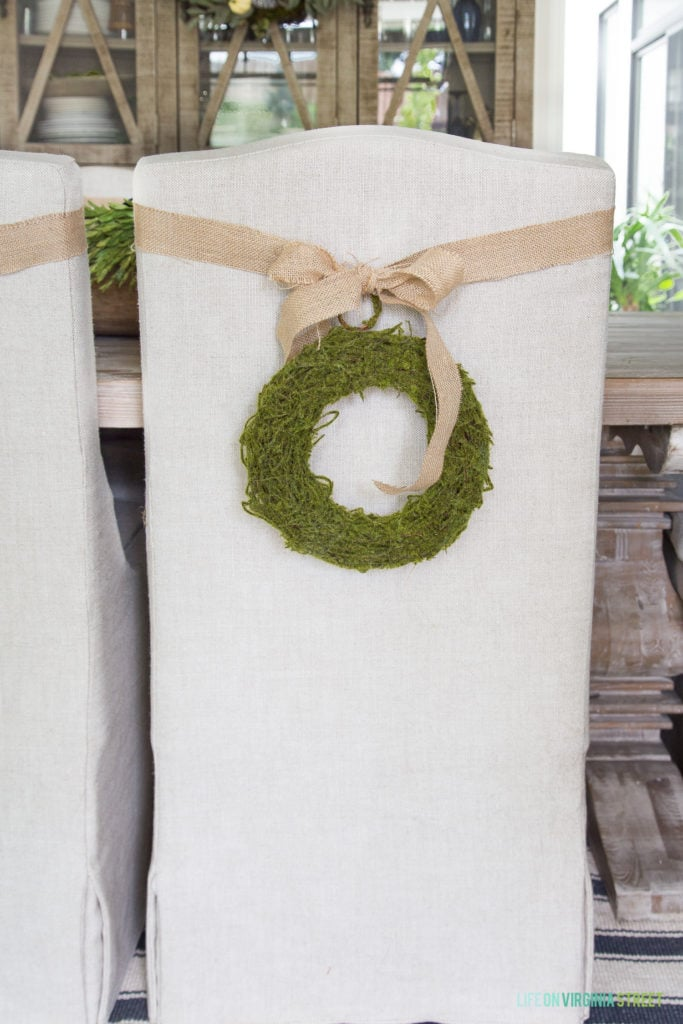 Burlap bow and green wreath on a white chair in the dining room.