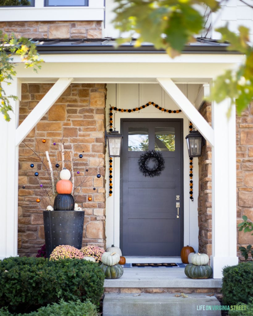 A Halloween porch featuring a DIY faux pumpkin topiary. Get the full tutorial as well as all the other details on this cute orange and black Halloween porch look!