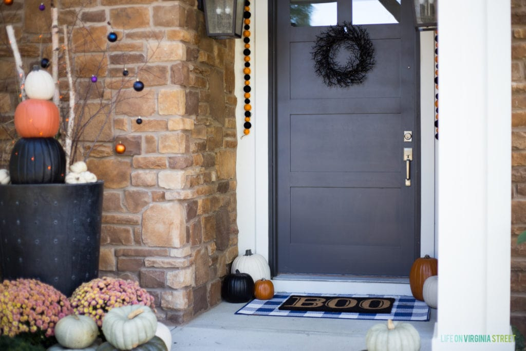 The front door with a black wreath on it and a boo welcome mat.