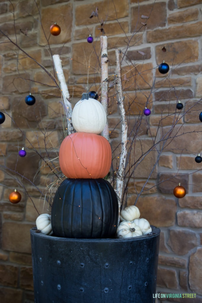 The funkin pumpkins in a black planter with decorated branches of purple gold and blue baubles.