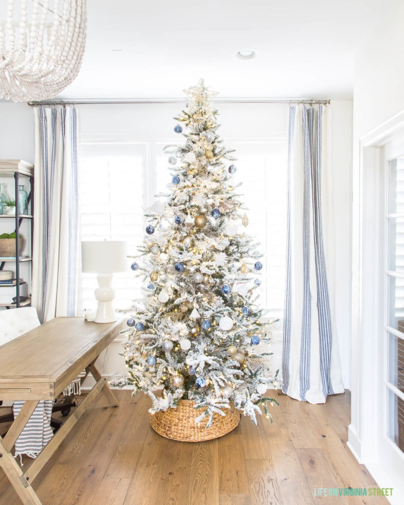 Blue, white and gold flocked Christmas tree on wooden floor in front of window.