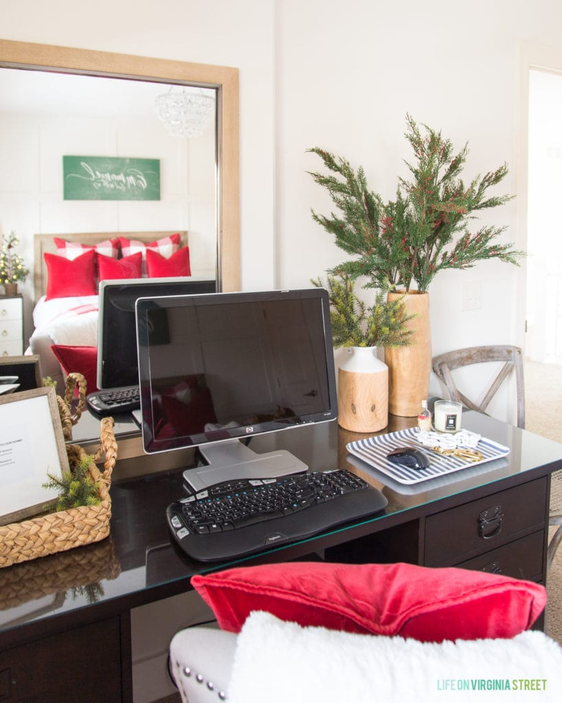 Computer on the desk with greenery in a vase beside it.