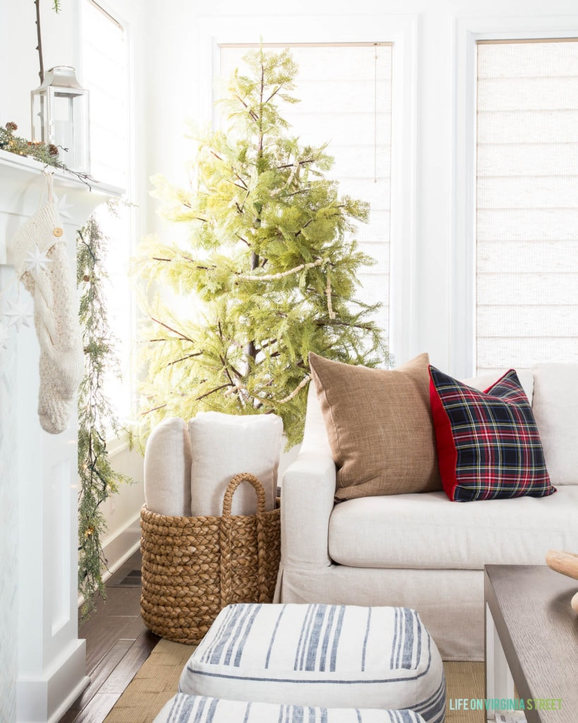 A linen sofa with brown linen pillow, black Stewart plaid pillow, a faux Cypress tree, a woven natural basket, silver lanterns, and chunky knit stockings are perfect in this Christmas living room!