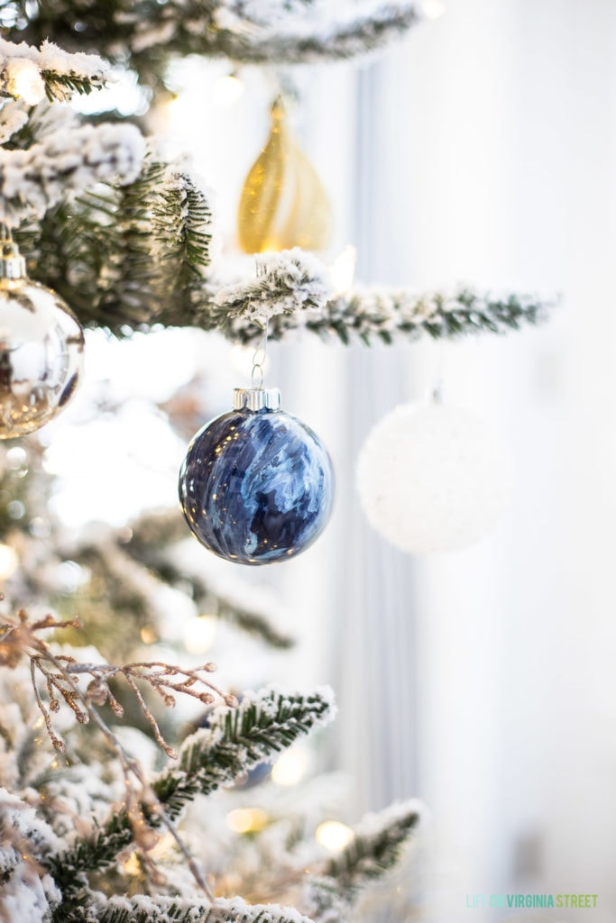Blue marbled ornament hanging on the Christmas tree.