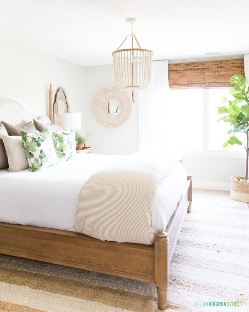 Beautiful green and neutral bedroom with a white bead chandelier.