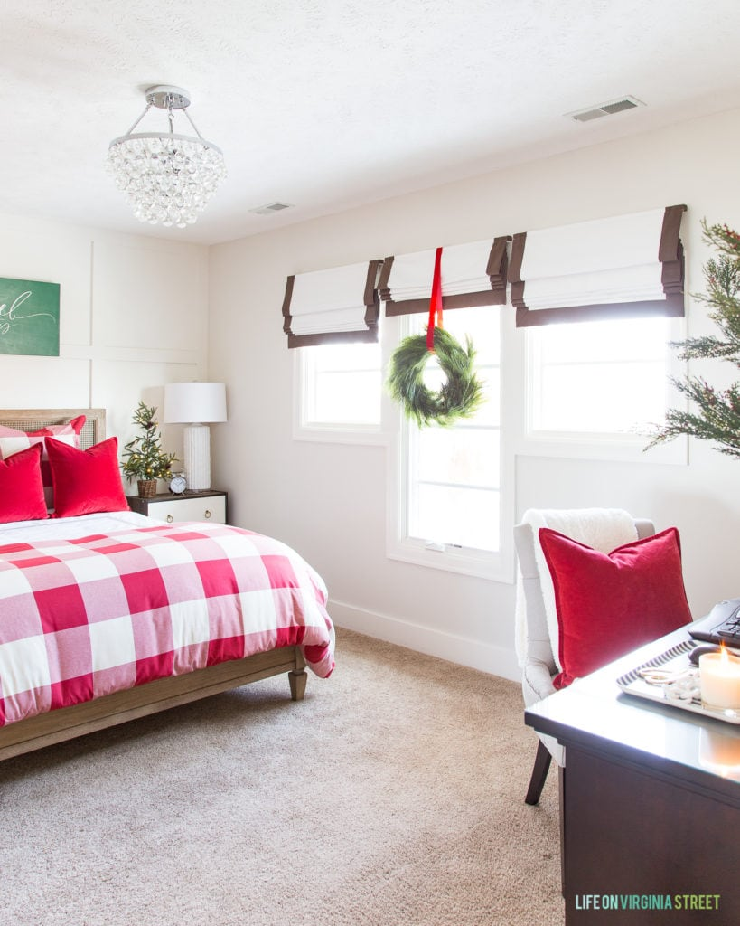 Beautiful red and white guest bedroom that's perfect for Christmas and the holidays! Red and white buffalo check duvet cover, red velvet pillows, faux pine tree, green wreath on windows and more!