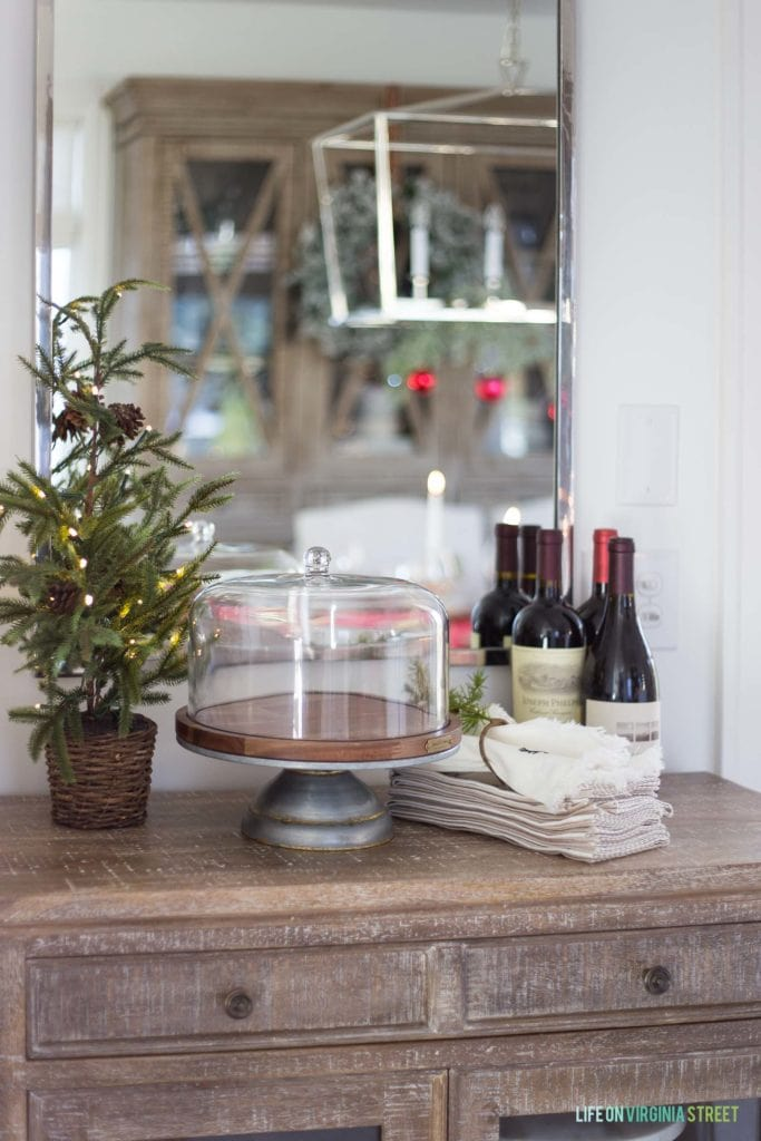 A Christmas buffet table with faux lit pine tree, a wood and metal cake stand, and linen napkins. Bottles of wine sit beside the napkins.